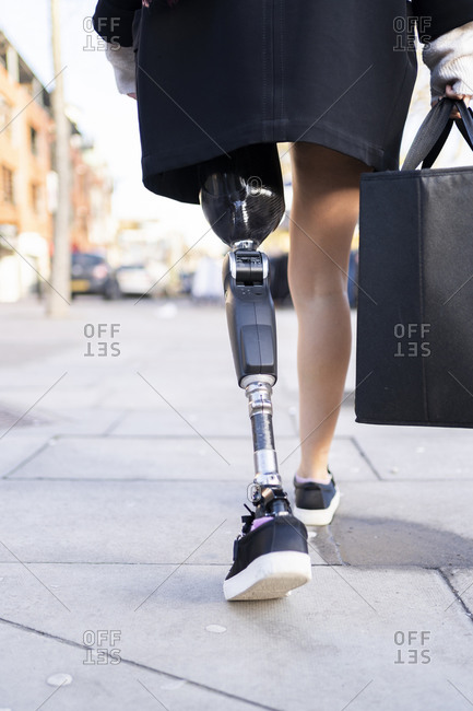 Low section of woman with leg prosthesis walking in the city