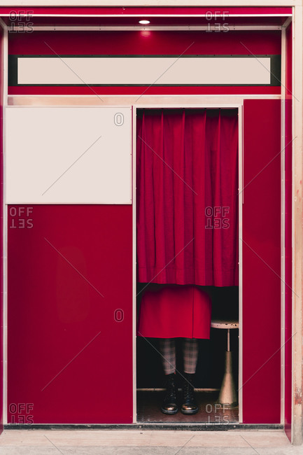 Woman wearing red coat and boots standing behind curtain in a photo booth