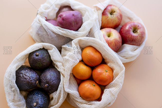 Eco-friendly reusable mesh bags with fresh fruits and vegetables