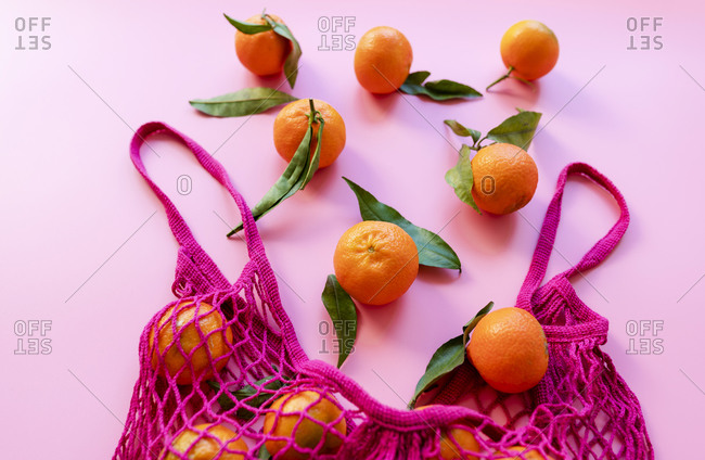 Studio shot of ripe clementines and eco-friendly reusable mesh bag