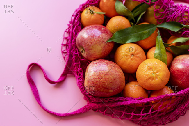 Fresh clementines and apples in eco-friendly reusable mesh bag
