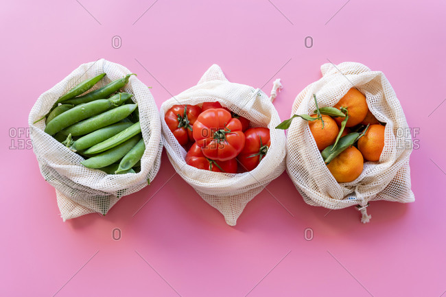 Eco-friendly reusable mesh bags with fresh green peas- tomatoes and clementines