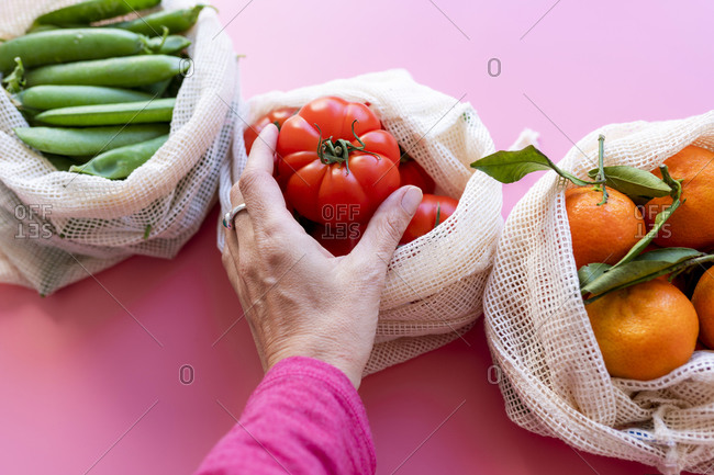 Hand of woman picking up fresh tomato from eco-friendly reusable mesh bag
