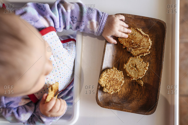 Baby girl sitting in high chair eating homemade oatmeal cookies with hands- top view