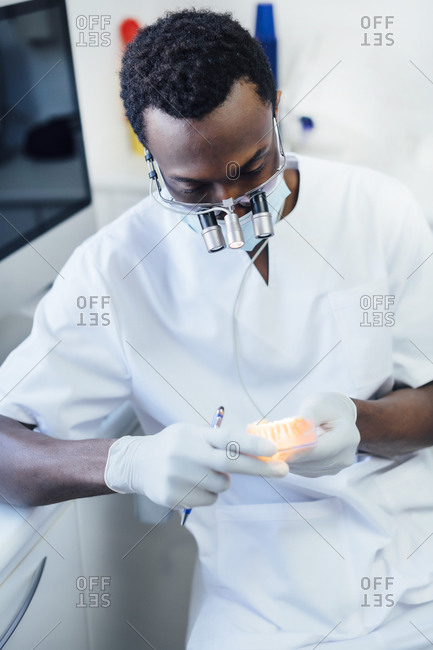 Dentist with loupe and mask working on dentures in his medical practice