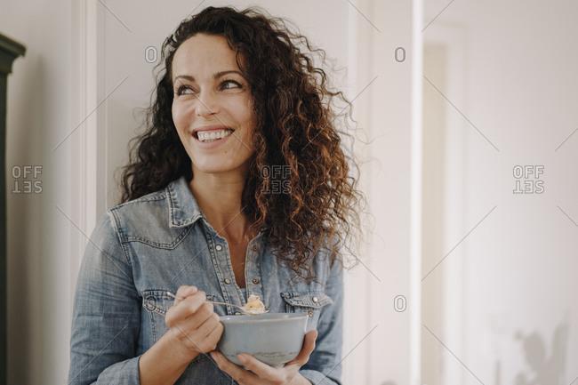 Beautiful woman having healthy breakfast- eating granola