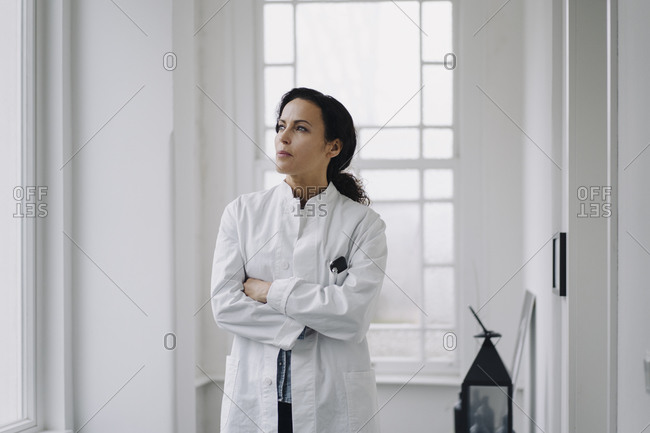 Female doctor standing at the window- looking worried