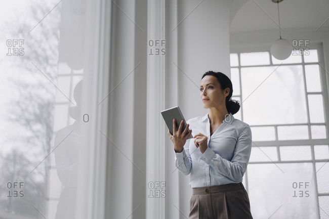 Successful businesswoman- standing by window- using digital tablet