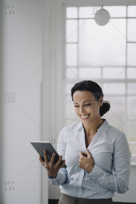 Successful businesswoman- standing by window- using digital tablet- smiling