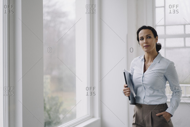 Successful businesswoman- standing by window- carrying laptop
