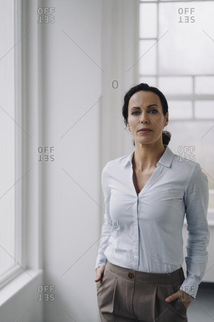 Successful businesswoman- standing by window- with hands in pockets