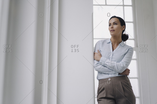 Successful businesswoman- standing by window- leaning on wall- thinking
