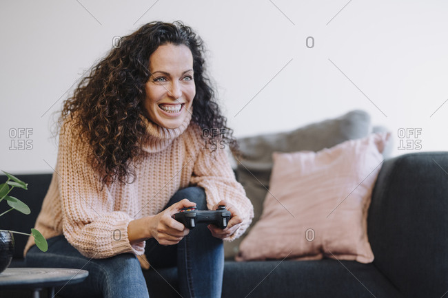 Woman sitting on couch- having fun- playing with a gaming console