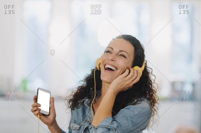 Happy woman listening music- singing and dancing- using smartphone and headphones