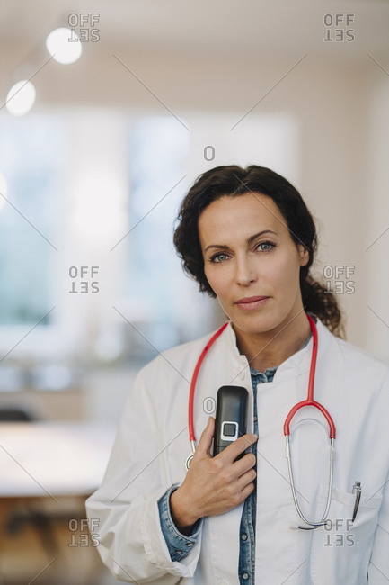 Female doctor standing in hospital- holding telephone and stethoscope