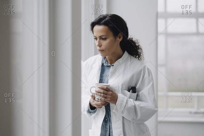 Female doctor standing at the window- looking worried- holding cup of coffee