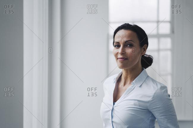 Successful businesswoman- standing by window- portrait