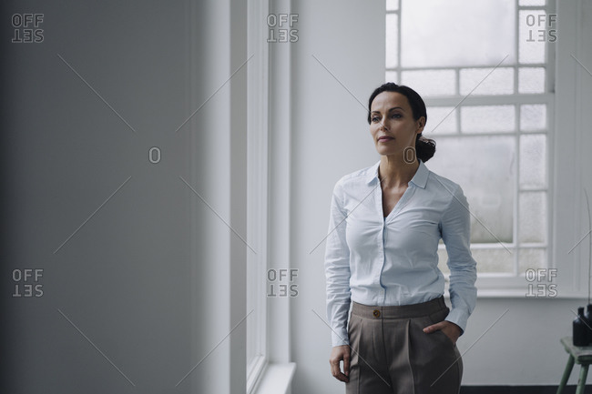 Successful businesswoman- standing by window- with hand in pocket