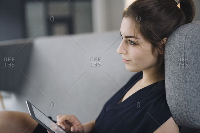 Young businesswoman sitting on couch with digital tablet looking at distance