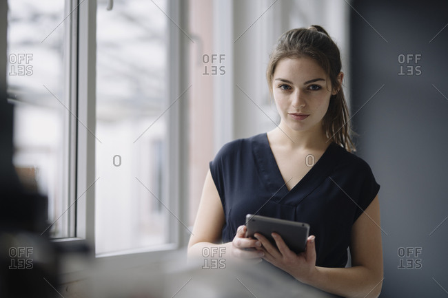 Portrait of young businesswoman with digital tablet in office