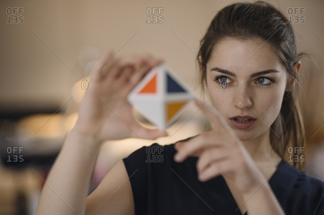 Portrait of young woman organizing time management with cube