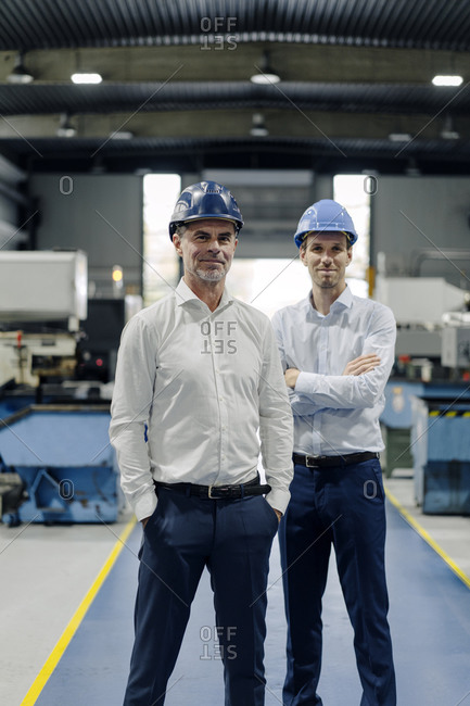 Portrait of two confident men wearing hard hats in a factory