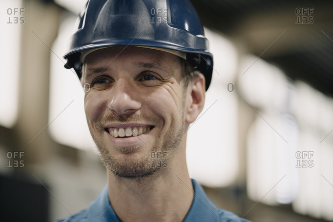 Portrait of a smiling worker in a factory wearing hard hat