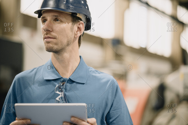 Portrait of a worker in a factory wearing hard hat and holding tablet