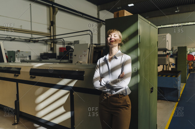 Businesswoman with closed eyes leaning against a cabinet in a factory