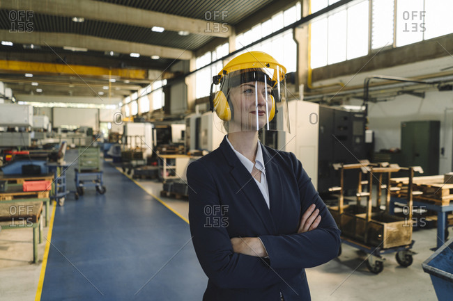 Portrait of a confident businesswoman wearing safety helmet and earmuffs in a factory