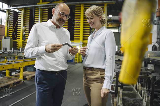 Man and woman examining workpiece in factory