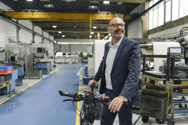 Smiling businessman with bicycle in a factory
