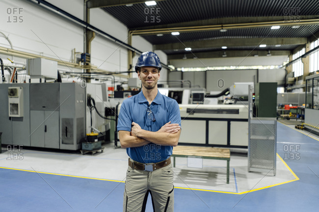 Portrait of a confident worker in a factory wearing hard hat