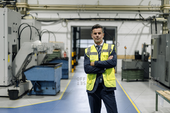 Portrait of a confident businessman wearing a reflective vest in a factory