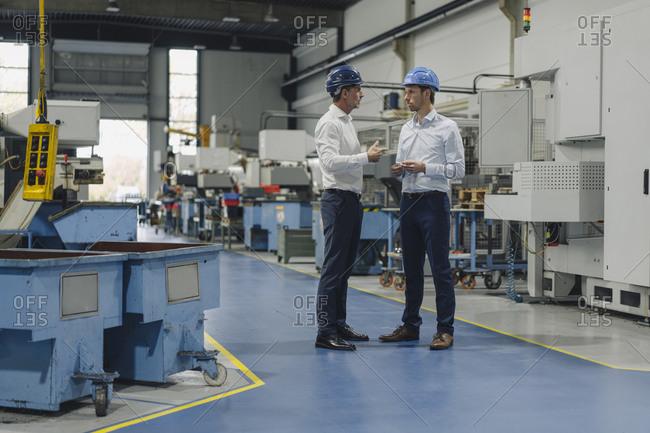 Two men wearing hard hats talking in a factory