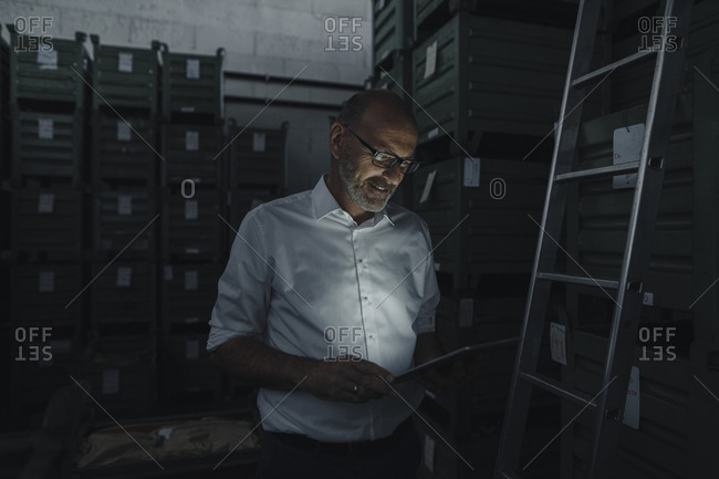 Businessman using tablet in a factory in the dark
