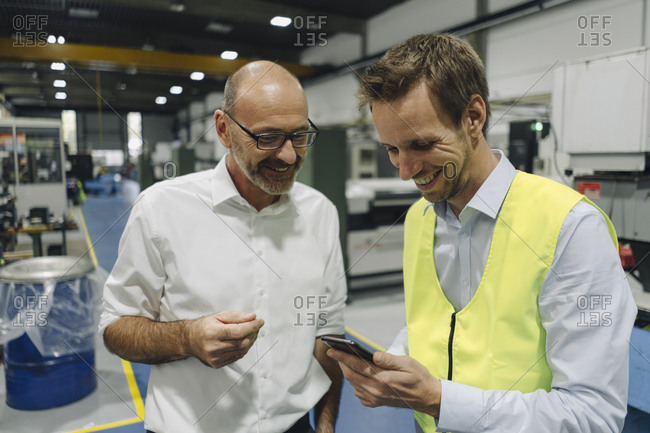 Businessman and man in reflective vest using smartphone in a factory