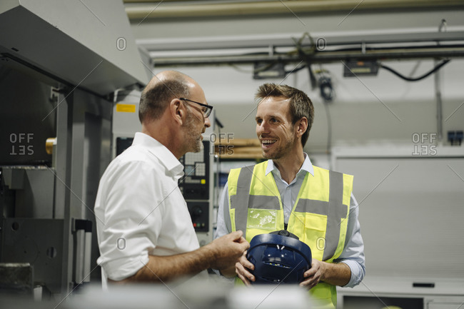Businessman talking to smiling man in reflective vest in a factory