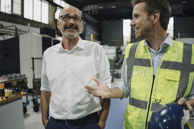 Businessman and man in reflective vest talking in a factory
