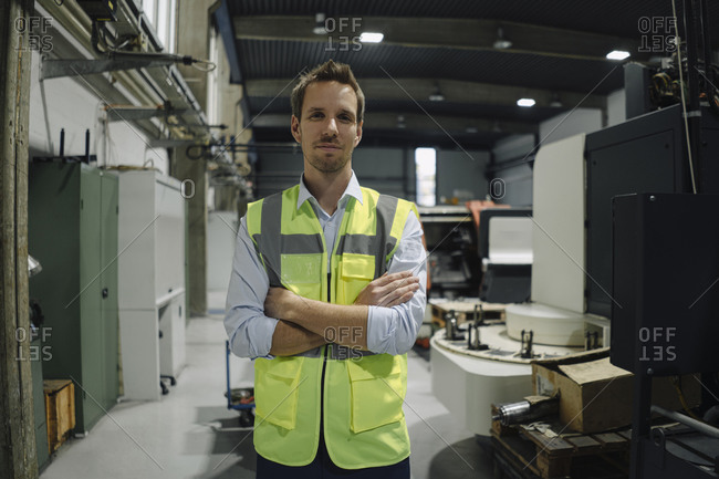 Portrait of a confident man wearing reflective vest in a factory