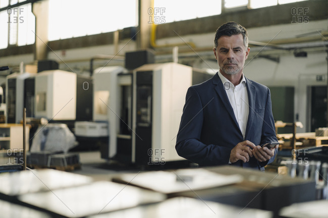 Portrait of a businessman with cell phone in a factory