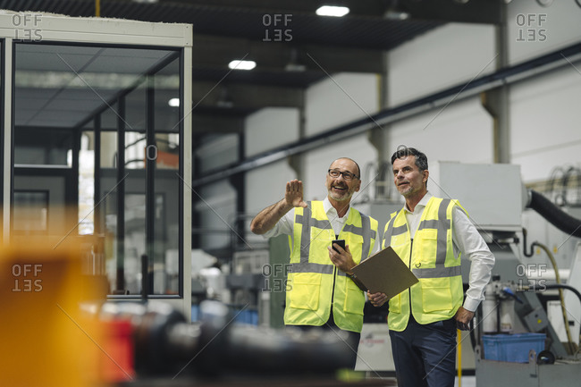 Two men in reflective vests talking in a factory