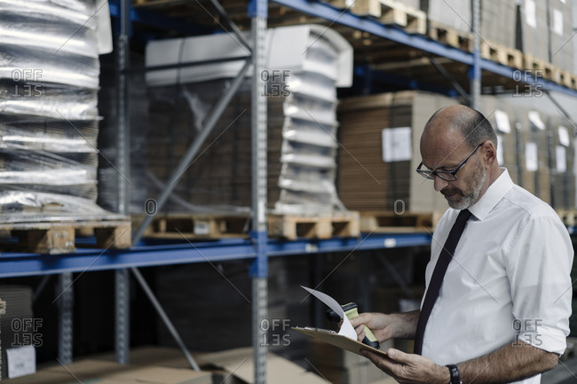Man with clipboard and scanner in factory warehouse