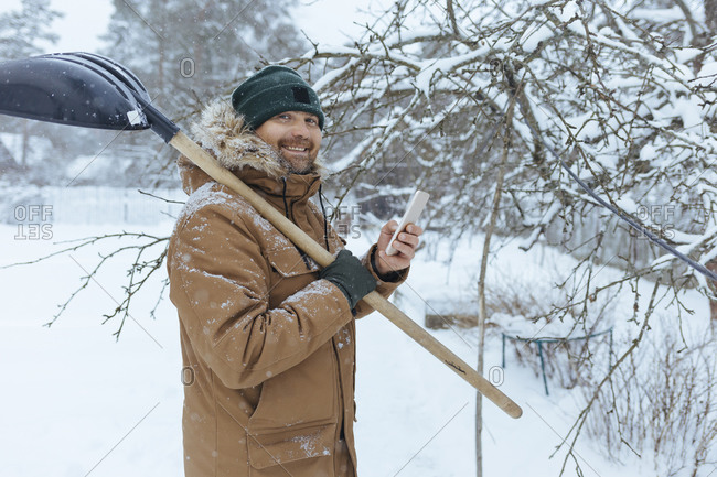 Portrait of smiling man with snow shovel and cell phone