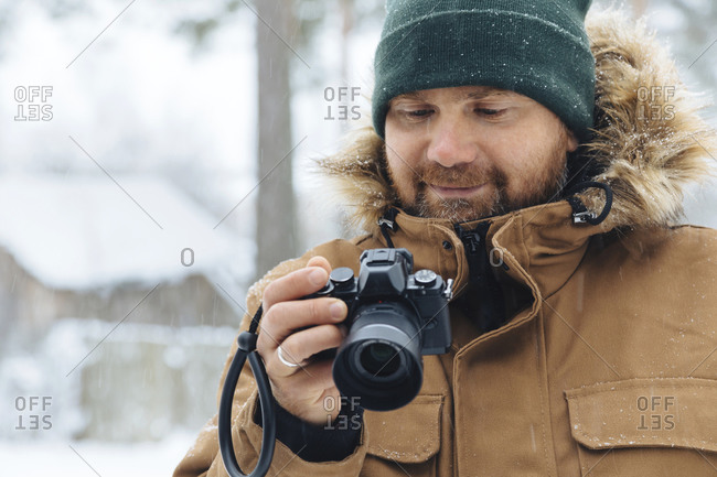 Portrait of smiling man looking at digital camera in winter