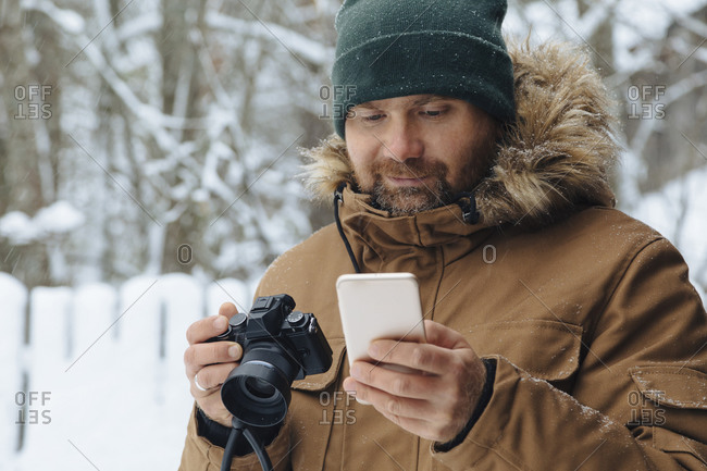 Portrait of bearded man looking with digital camera looking at cell phone in winter
