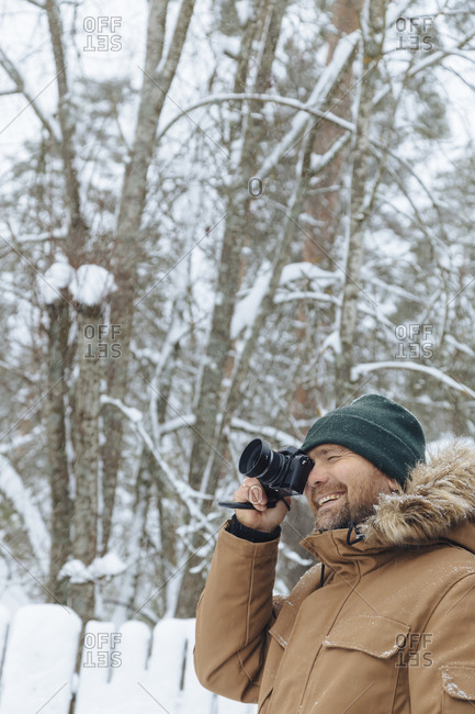 Portrait of smiling man taking photo with digital camera in winter forest