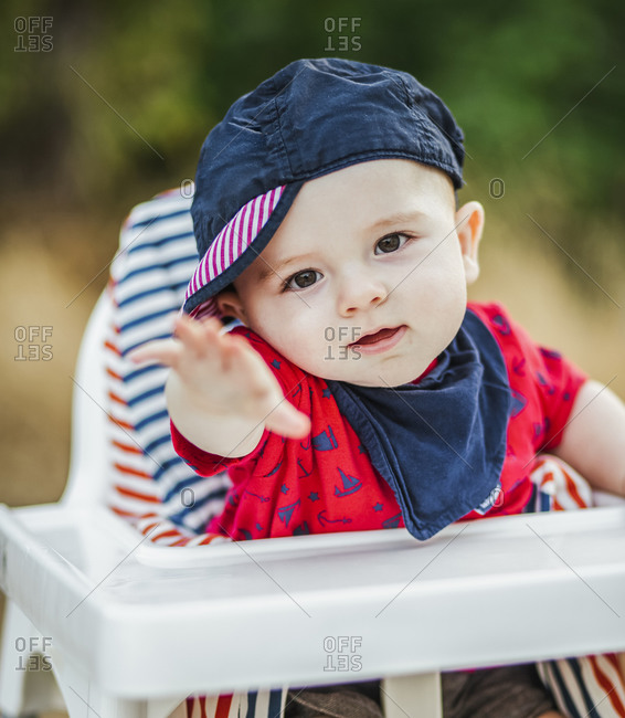 Portrait of baby boy wearing cap and scarf sitting in high chair