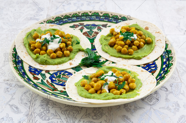 Plate of pita breads with mashed avocados- turmeric chick-peas- yogurt and parsley