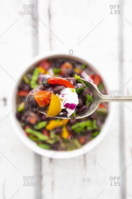 Spoon of black bean soup with bell pepper- cilantro- sour cream and red onions